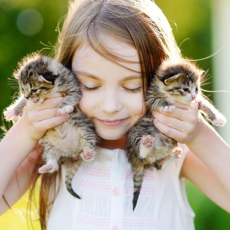 Förtjusande liten flicka som spelar med små kattungar royaltyfri foto
