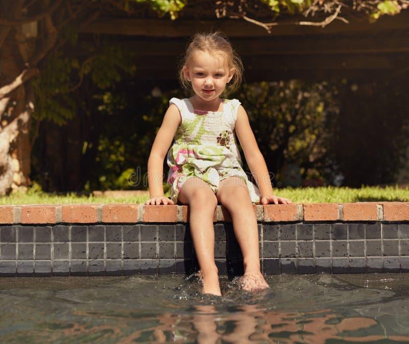 Förtjusande liten flicka som tycker om att sitta vid kanten av pölen royaltyfri fotografi