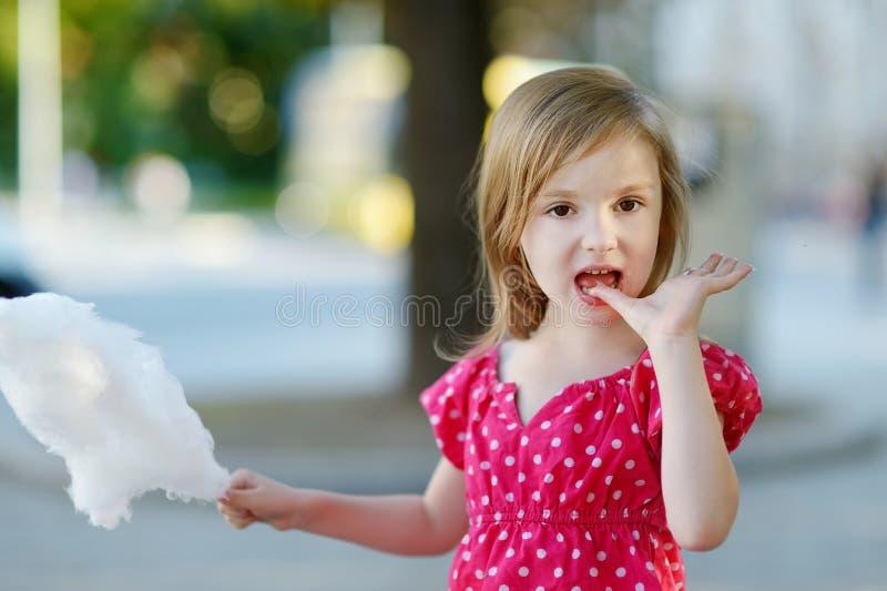 Förtjusande liten flicka som utomhus äter godis-floss royaltyfria foton