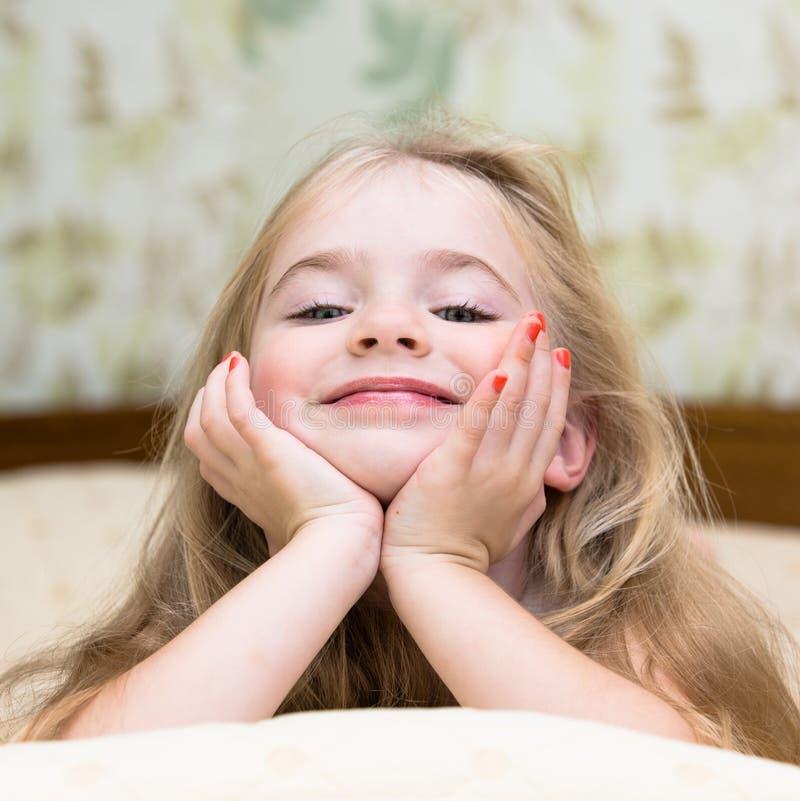 Förtjusande liten flicka som vaknas upp i säng royaltyfri foto