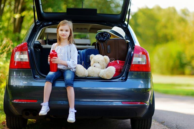 Förtjusande liten flickadricksvatten i en bil royaltyfria bilder