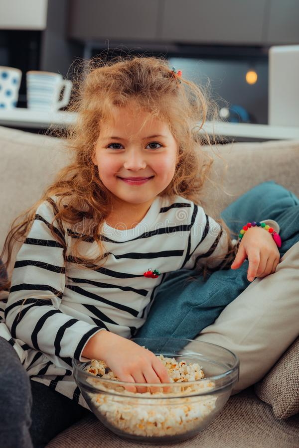 Förtjusande liten långhårig flicka med ett ljust armband som äter popcorn royaltyfri fotografi