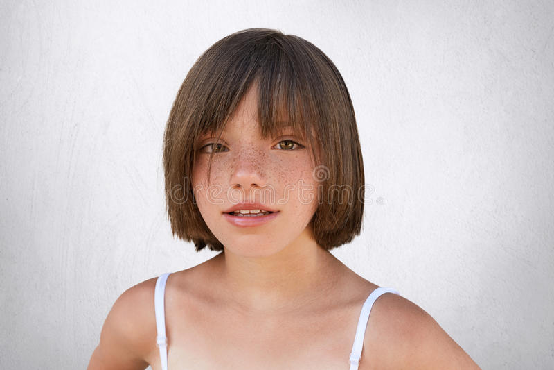 Förtjusande litet barn med bruna charma ögon, fräknig hud och tunna kanter som har den stilfulla frisyren, bärande sommarkläder s royaltyfria bilder