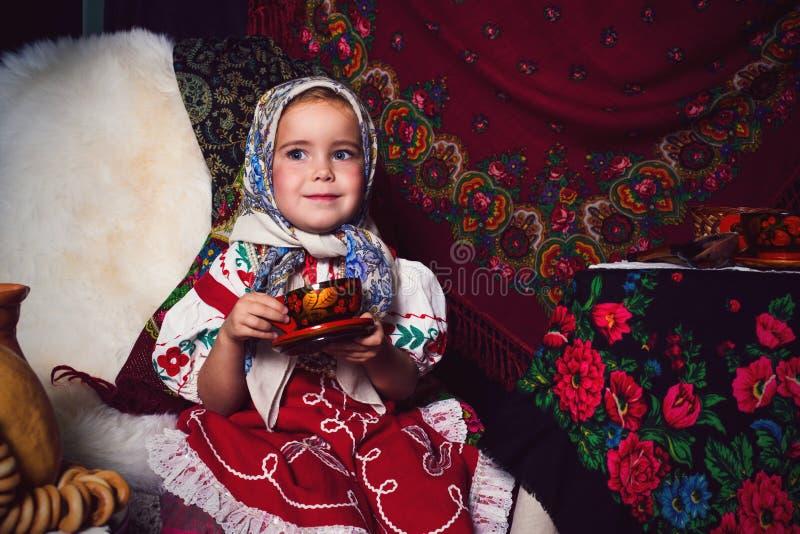 Förtjusande litet barnflicka som bär den nationella klänningen på tebjudningen royaltyfria bilder