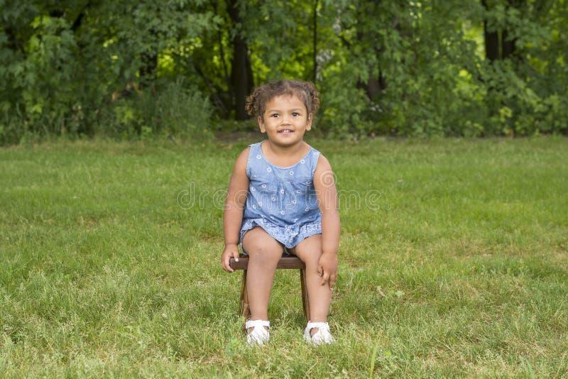 Förtjusande litet barnflickasammanträde på en stol arkivbilder