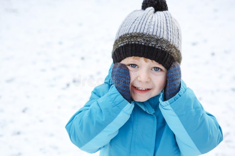 Förtjusande litet barnpojke som har gyckel med snö på vinterdag arkivfoto