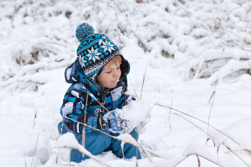 Förtjusande litet barnpojke som har gyckel med snow arkivfoton