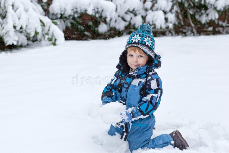 Förtjusande litet barnpojke som har gyckel med snow arkivfoto
