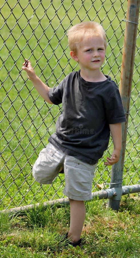 Förtjusande litet barnpojkeanseende på ett ben royaltyfria bilder