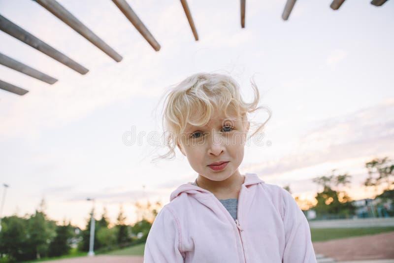 Förtjusande litet blont Caucasian flickabarn som gör den roliga enfaldiga framsidan royaltyfri fotografi