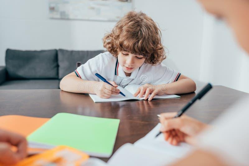 förtjusande lockig pojke som gör läxa med den suddiga systern arkivfoto