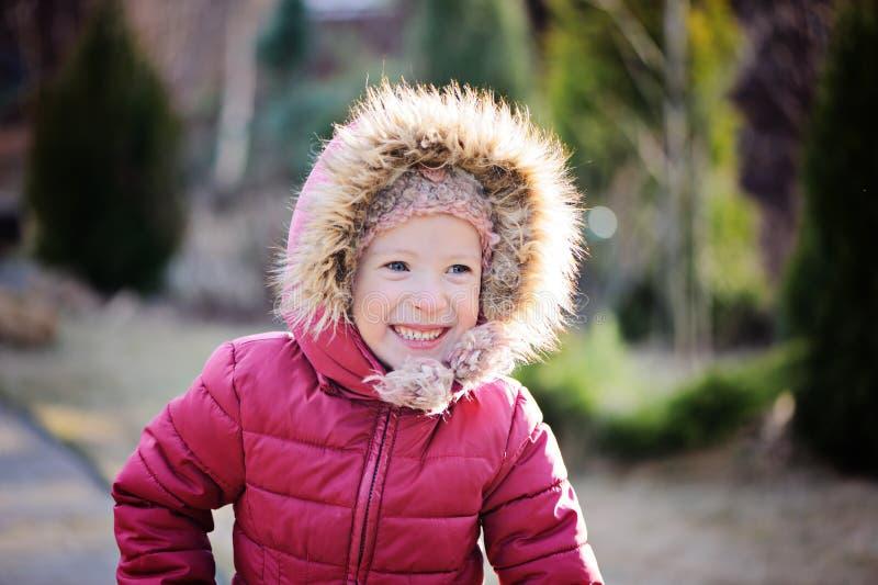 Förtjusande lycklig barnflickastående i solig vårträdgård royaltyfri bild