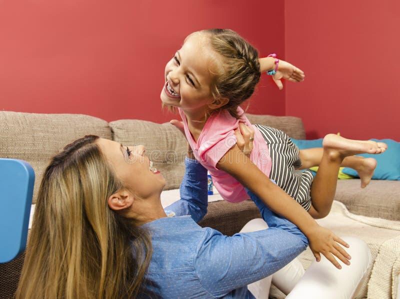 Förtjusande lycklig luft för liten flickaflygkast i hennes moderarmar royaltyfri bild