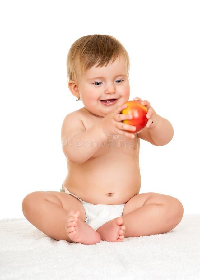 Förtjusande lyckligt behandla som ett barn med äpplet arkivbild