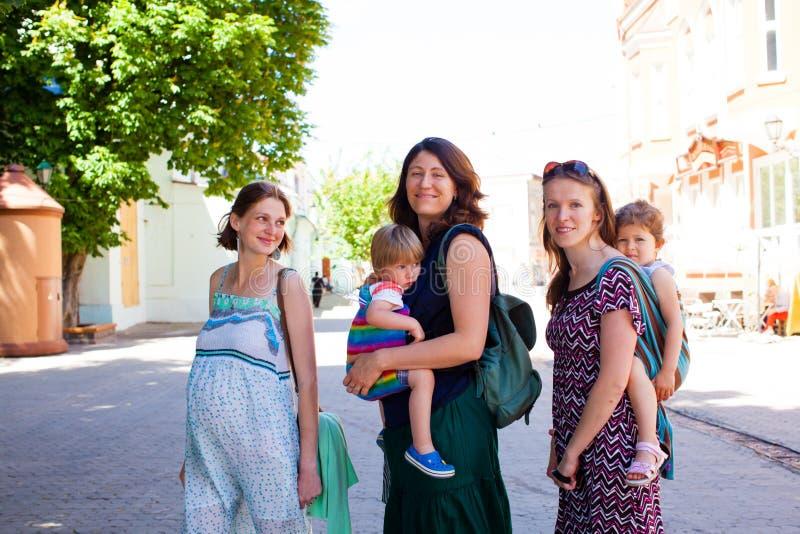 Förtjusande mödrar som står på staden, parkerar fotografering för bildbyråer