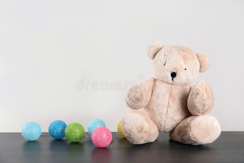 Förtjusande nallebjörn och färgrik girland på tabellen mot ljus bakgrund, utrymme för text royaltyfri foto