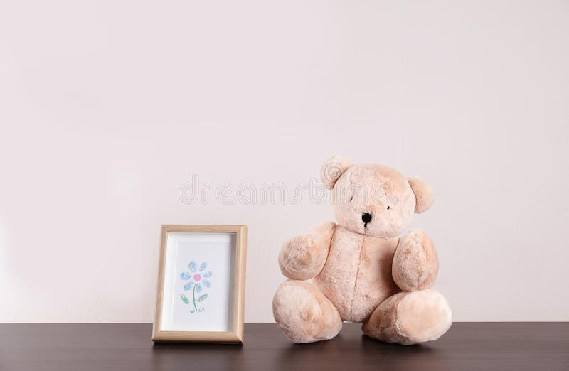 Förtjusande nallebjörn och ram med den gulliga bilden på tabellen mot ljus bakgrund, utrymme för text royaltyfri fotografi