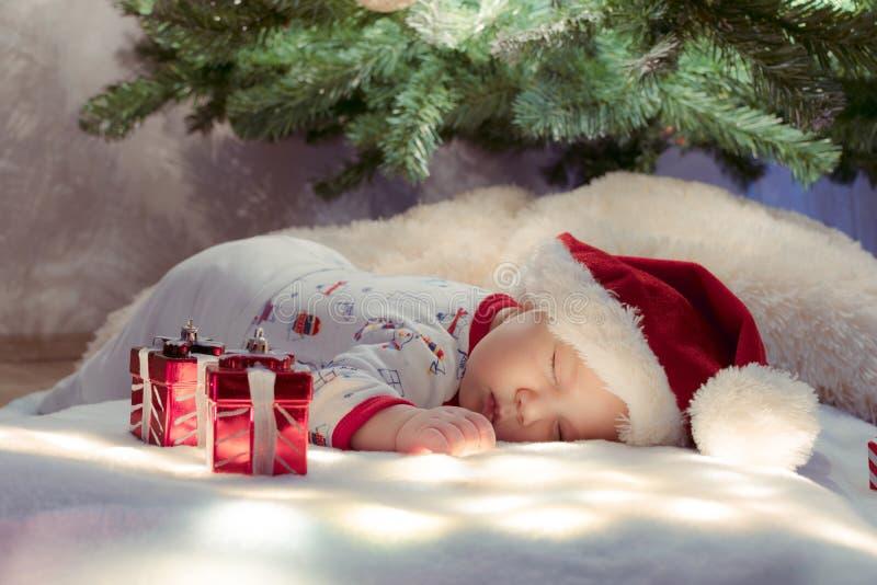 Förtjusande nyfött behandla som ett barn att sova under julgranen nära gåvor på belysningfilten arkivbilder