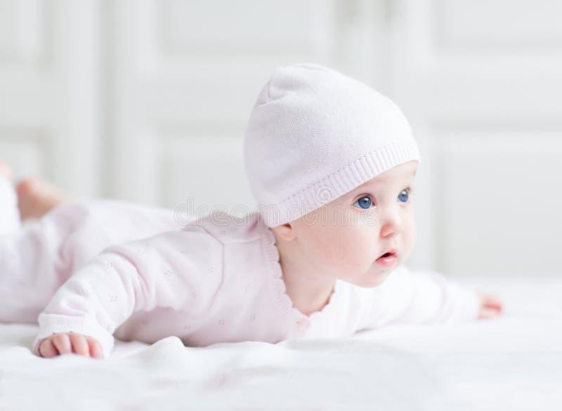 Förtjusande nyfött behandla som ett barn flickan i en rosa färger knited hatt royaltyfri foto