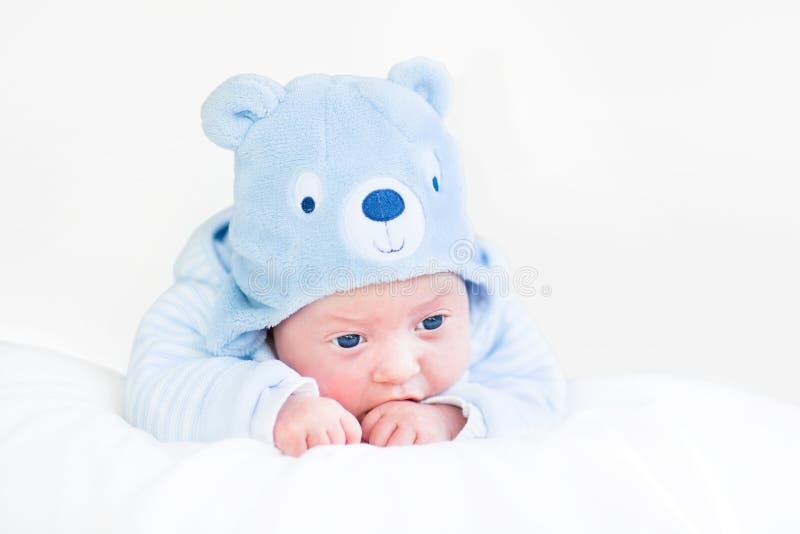 Förtjusande nyfött behandla som ett barn pojken i blå hatt för nallebjörn royaltyfri bild
