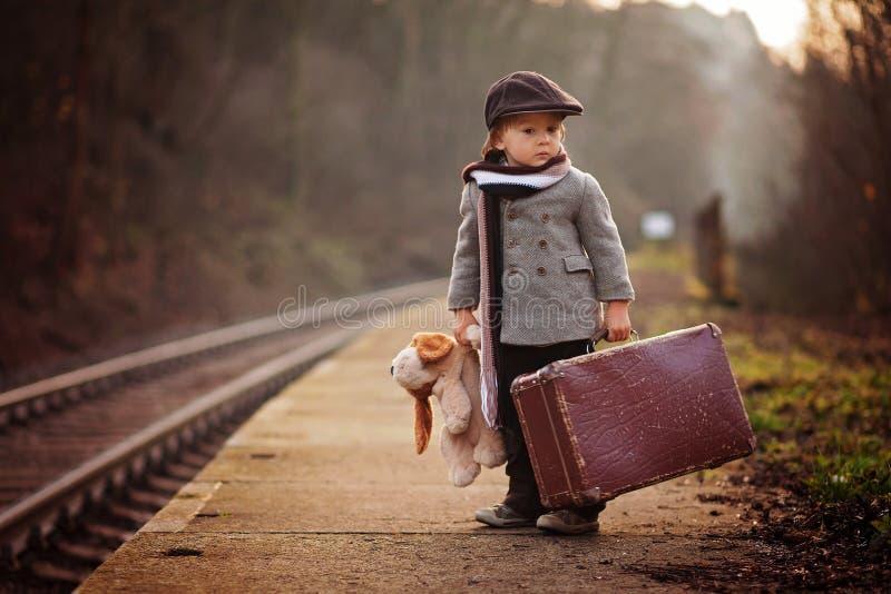Förtjusande pojke på en järnvägsstation och att vänta på drevet med resväskan och nallebjörnen royaltyfri foto