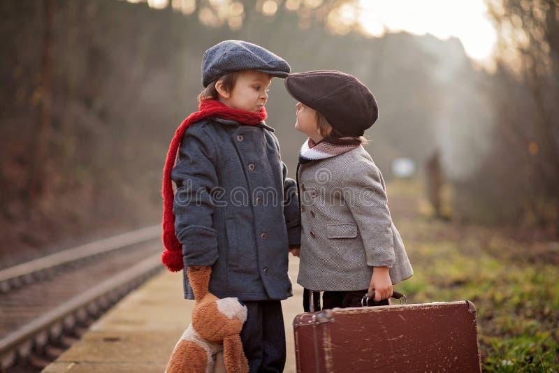 Förtjusande pojke på en järnvägsstation och att vänta på drevet med resväskan och nallebjörnen royaltyfri bild