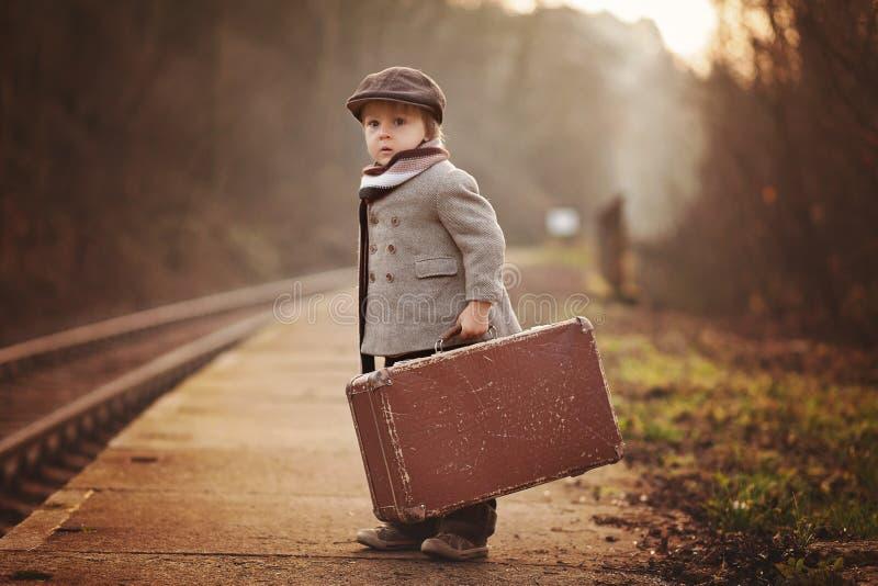 Förtjusande pojke på en järnvägsstation och att vänta på drevet med resväskan och nallebjörnen royaltyfri fotografi