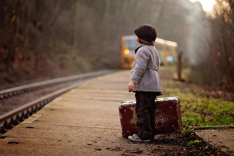 Förtjusande pojke på en järnvägsstation och att vänta på drevet med resväskan och nallebjörnen royaltyfria bilder