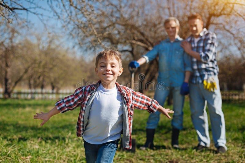 Förtjusande pojke som har gyckel i trädgård royaltyfria foton