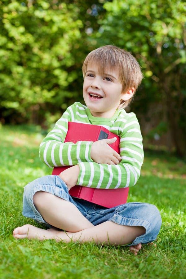 Förtjusande pojke som omfamnar en bok arkivbilder