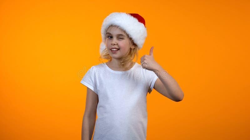 Förtjusande preteen flicka i den santa hatten som visar tumme-oss och blinkar till kameran fotografering för bildbyråer
