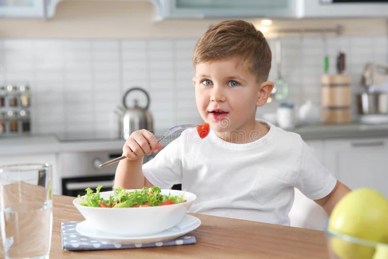 Förtjusande pys som äter grönsaksallad på tabellen arkivfoto
