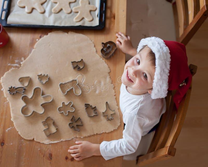 Förtjusande pys som förbereder kakor för jul arkivfoto