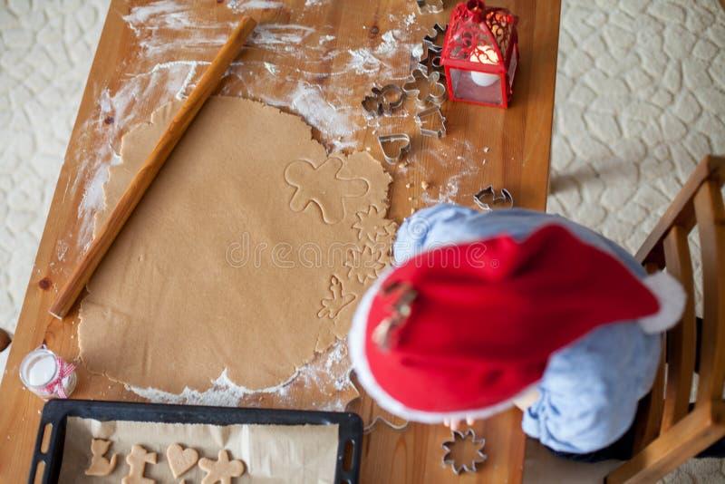 Förtjusande pys som hemma förbereder kakor för jul royaltyfri bild