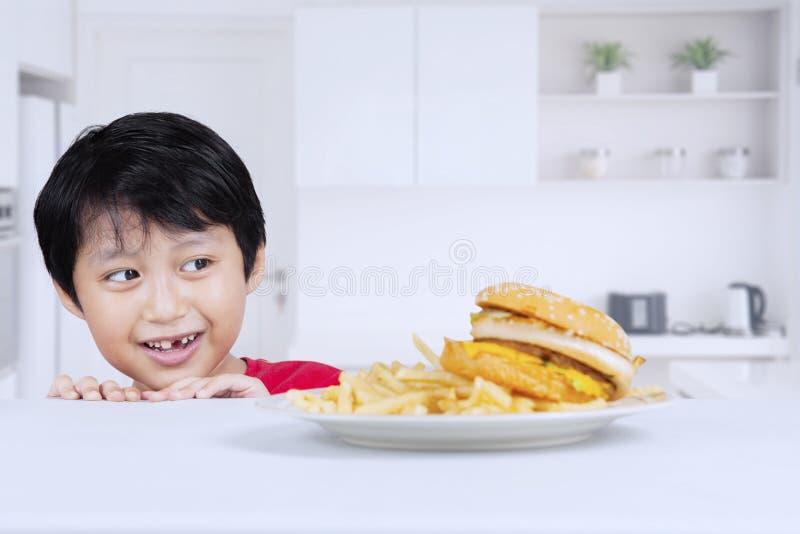 Förtjusande pys som kikar en läcker hamburgare royaltyfri foto