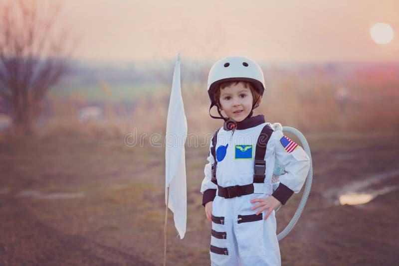 Förtjusande pys som kläs som astronautet som spelar i parkera w fotografering för bildbyråer