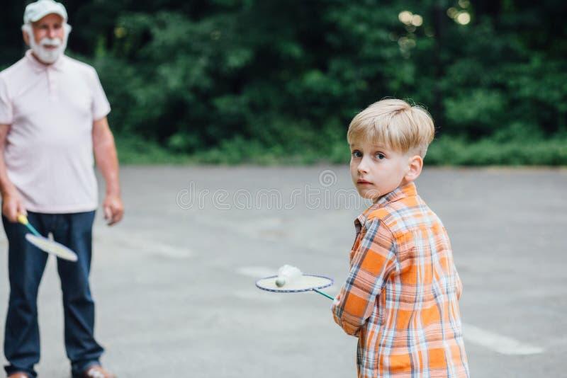 Förtjusande pys som spelar badminton med hans grandfater på lekplatsen Utomhus- sommaraktiviteter f?r ungar Familj Tid royaltyfria bilder