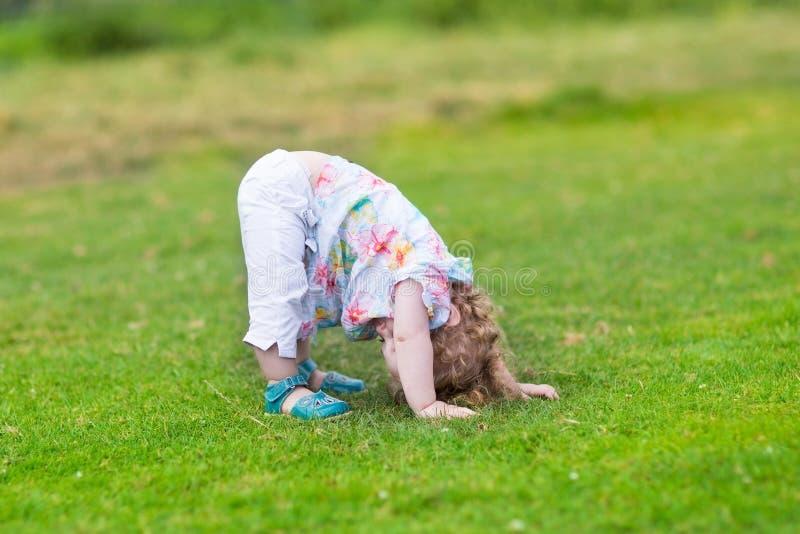 Förtjusande roligt behandla som ett barn flickan med hennes huvud ner royaltyfri foto