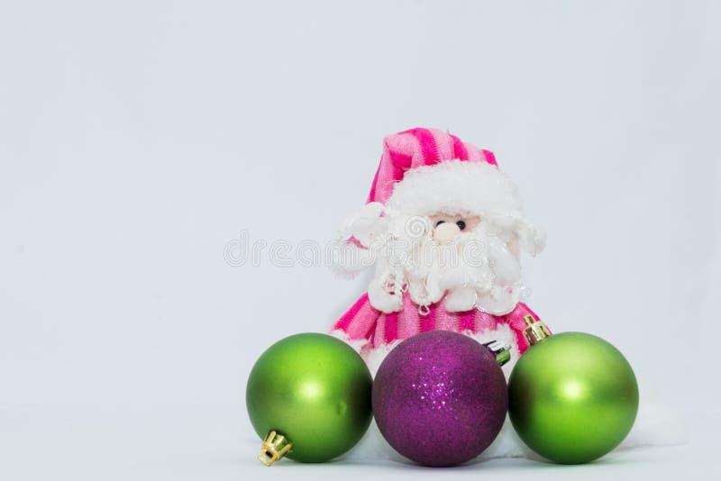 Förtjusande rosa Santa Claus med tre julsfärer och vit bakgrund arkivbilder