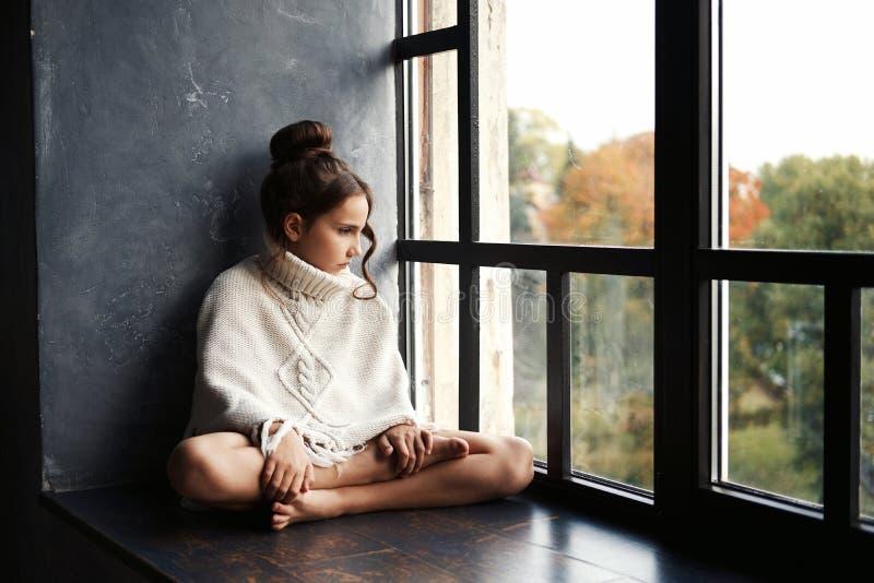 Förtjusande sammanträde för tonårs- flicka på en fönsterfönsterbräda som utanför ser till och med fönstret royaltyfri bild