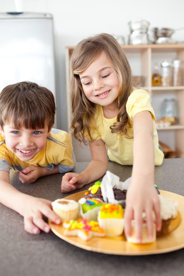 Förtjusande sibling som tar muffiner på en tabell royaltyfri fotografi