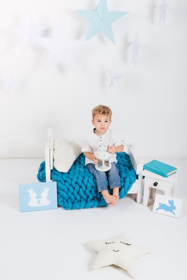 förtjusande sititng för liten unge på den blåa stack plädet med easter som hälsar kaninkort royaltyfria bilder