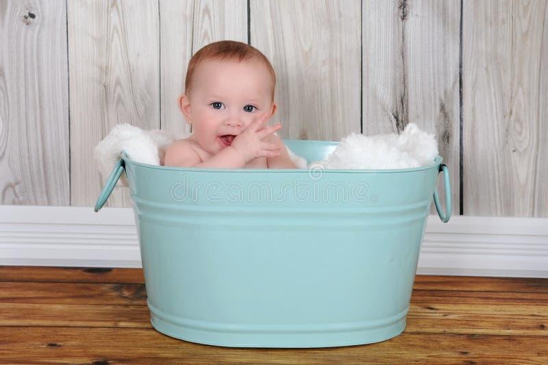 Förtjusande sitta barnvakt i hapily grön washtub fotografering för bildbyråer