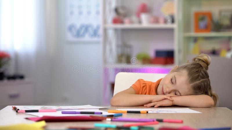 Förtjusande skolflicka som sover på skrivbordet, färgblyertspennor och papper på tabellutbildning royaltyfria foton
