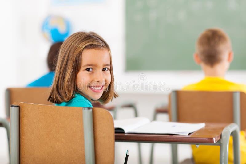 Förtjusande skolflickaklassrum arkivfoton