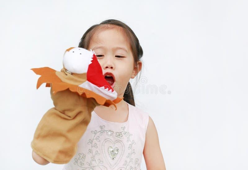 Förtjusande små asiatiska kläder för barnflickahand och spela lejondockor på vit bakgrund Utbildningsbegrepp royaltyfria bilder
