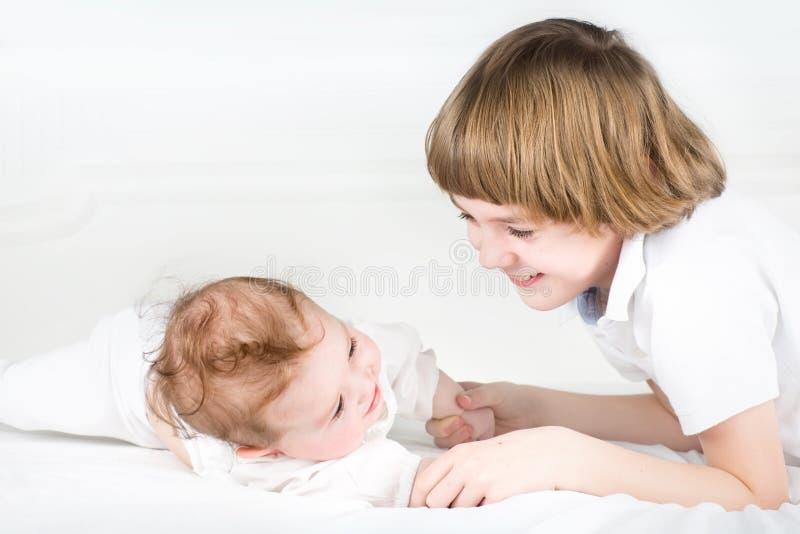 Förtjusande små behandla som ett barn flickan med hennes storebror arkivfoto