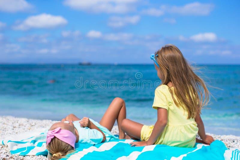 Förtjusande små flickor har gyckel på den vita stranden royaltyfria bilder