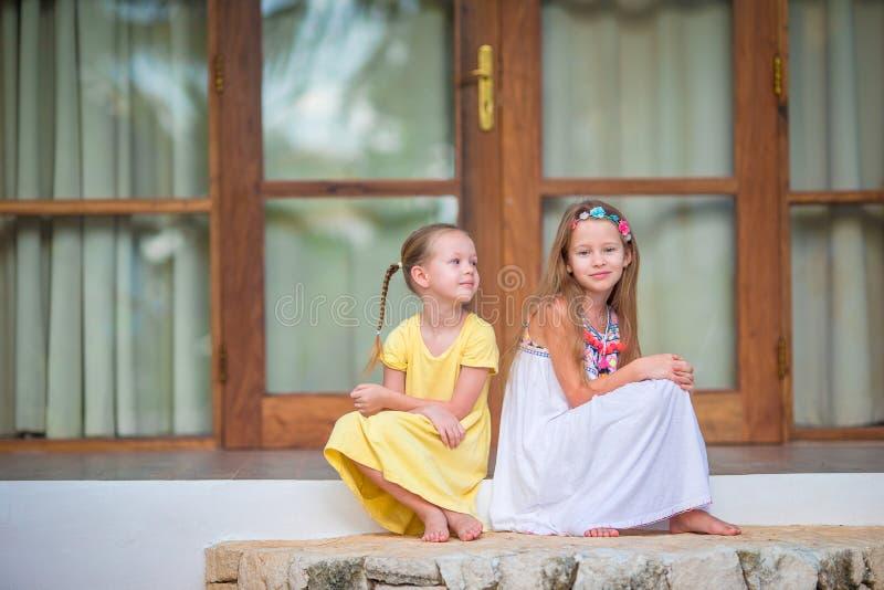 Förtjusande små flickor på terrass under sommarsemester fotografering för bildbyråer