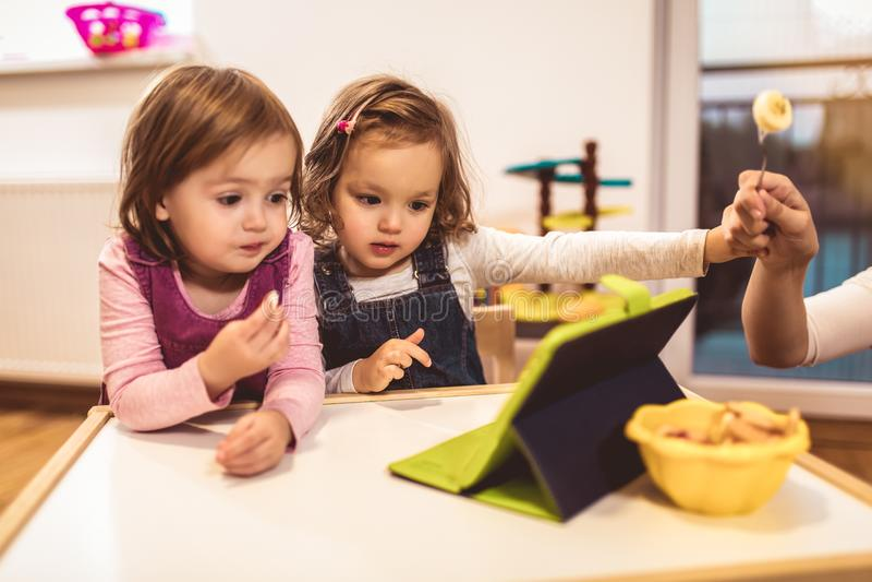 Förtjusande små systrar som spelar med en digital minnestavla på hom royaltyfri bild